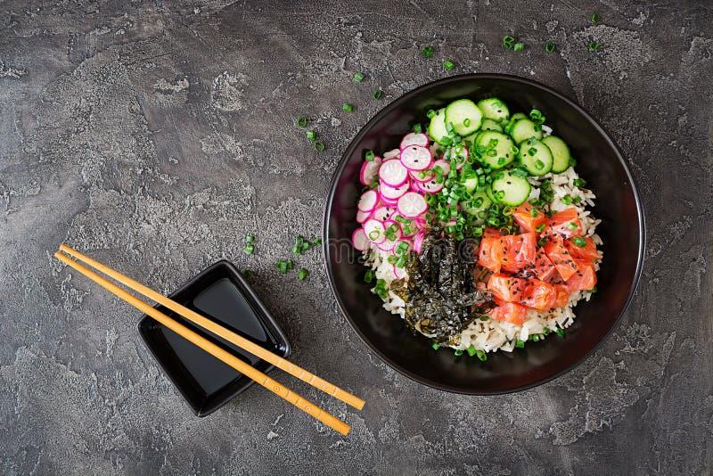 De Hawaiiaanse zalmvissen porren kom met rijst, radijs, komkommer, tomaat, sesamzaden en zeewieren royalty-vrije stock foto