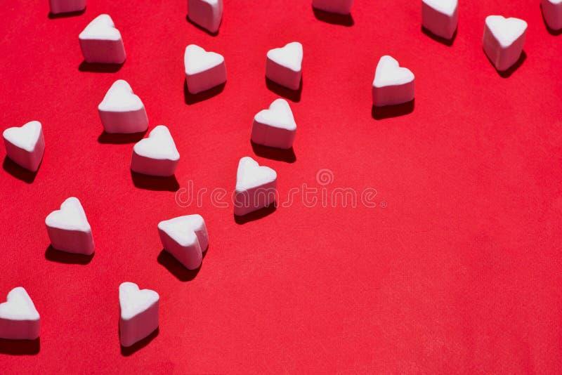 De heemst van het suikergoedharten van de valentijnskaartendag over rode achtergrond stock afbeelding