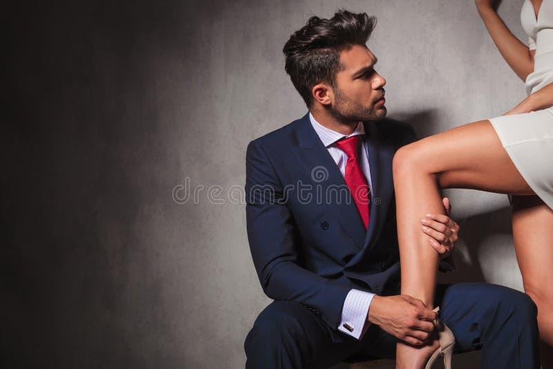 De heer helpt zijn vrouw om haar schoenen te worden stock foto