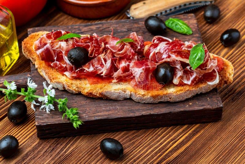 De heerlijke broodtoost met natuurlijke tomaat, extra eerste persing, Iberische ham, zwart olijven en basilicum gaat weg stock foto's