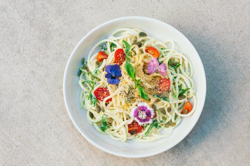 De heerlijke die salade van de courgettespaghetti met hennepzaden, spinazie, pompoenzaden, met bloemen, in kom worden verfraaid,  royalty-vrije stock afbeelding