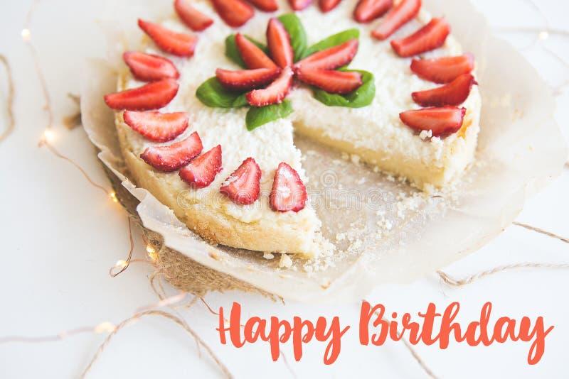 De heerlijke en heldere kaastaart versierde met verse aardbeien en groene basilicumbladeren, de inschrijving van gelukkig stock foto's