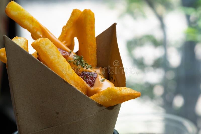 De heerlijke frieten die met cheddarkaas bedekken romen en knapperig bacon op dicht omhoog af zijaanzicht stock foto's