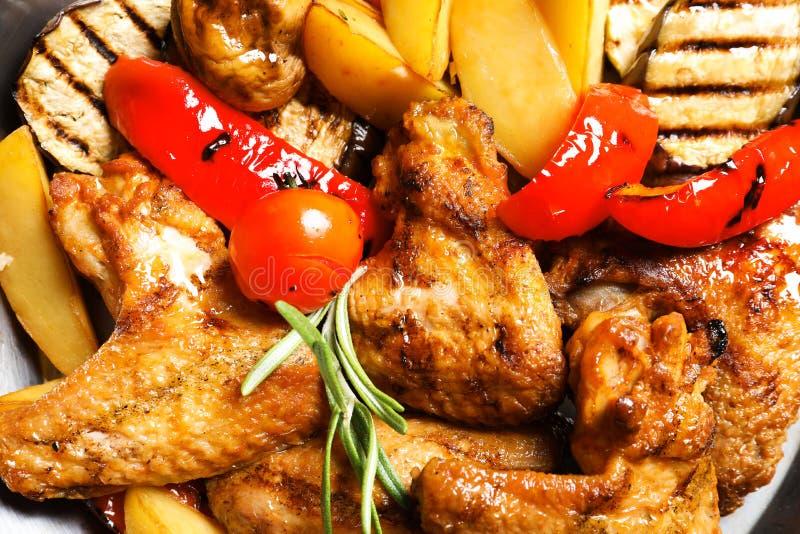 De heerlijke geroosterde kippenvleugels met versieren gediend in wok stock afbeelding