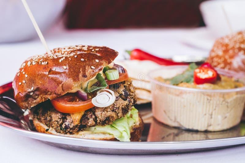 De heerlijke hamburger van de veganist zwarte boon met groenten en hummus, selectieve nadruk stock afbeeldingen