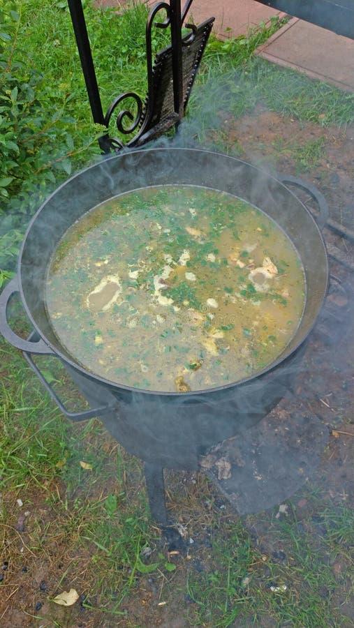 De heerlijke kippensoep is gekookt op een open brand in een zwarte gietijzerpot Een man hand probeert een soep met een gietlepel  royalty-vrije stock foto