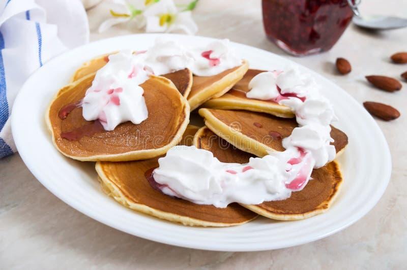 De heerlijke pannekoeken met frambozenjam en slagroom op een wit plateren op de keukenlijst stock foto's