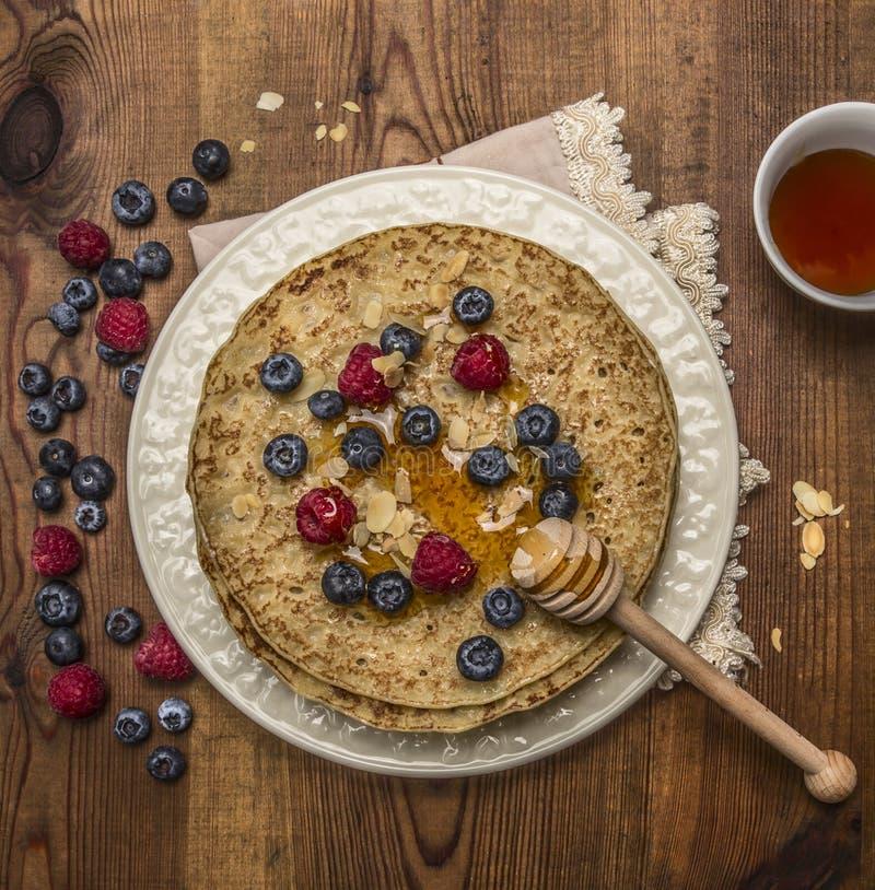 De heerlijke pannekoeken op een witte plaat met servet met honing en honing lepelen amandelenbosbessen en frambozen en een kop th stock afbeelding