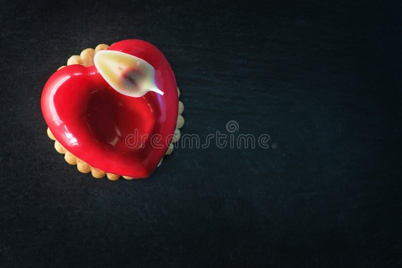 De heerlijke rode valentijnskaarten koeken met hartvorm op zwarte achtergrond, vakantiecake royalty-vrije stock foto