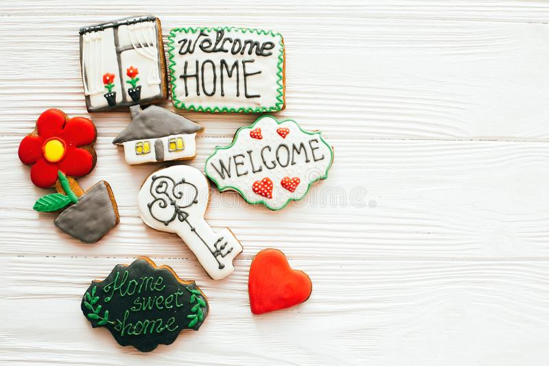 De heerlijke sleutel, huis, installatie, venster, hart en welkom tekenkoekjes op wit vlak hout, leggen met ruimte voor tekst Het  royalty-vrije stock foto