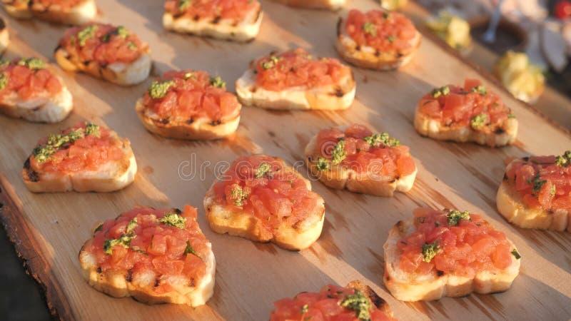 De heerlijke smakelijke tomaten Italiaanse voorgerechten, of bruschetta, op plakken van geroosterde baguette, verfraaiden met nat stock foto's