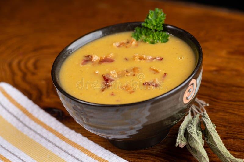 De heerlijke soep van de butternutpompoen met baconbeetjes stock foto's