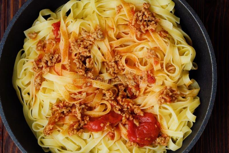 De heerlijke tagliatelledeegwaren met hakken en tomaten in een pan fijn stock foto's