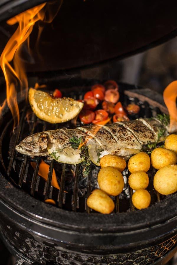 De heerlijke vissen van de regenboogforel met tomaten, aardappels en citroen het koken bij de hete vlammende grill Barbecue Resta stock fotografie