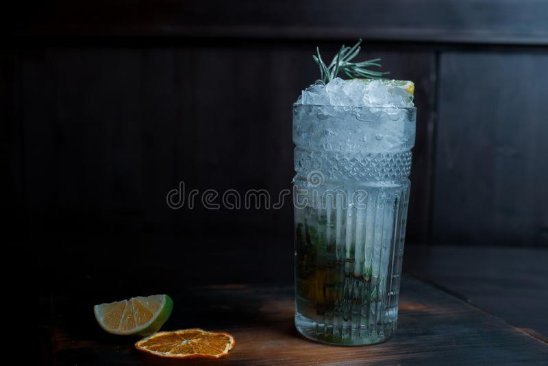 De heerlijke zoete mojitococktail met tonicum en met wodka met stukken van ijs met plakken van fruit en verse munt bevindt zich i royalty-vrije stock fotografie