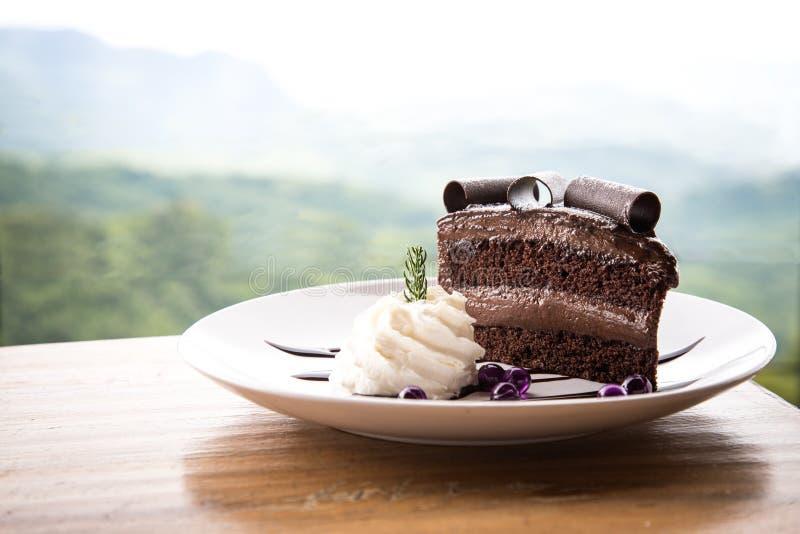 De heerlijke zwarte chocoladecake met ranselt room op witte schijf stock foto