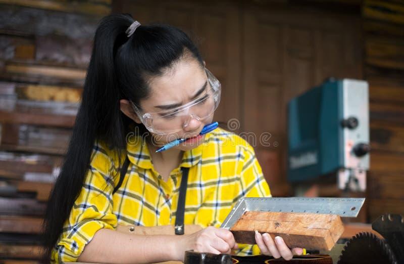 De heerser en het potlood van de vrouwenholding terwijl het maken van tot tekens op het hout de lijst in de workshop royalty-vrije stock foto's