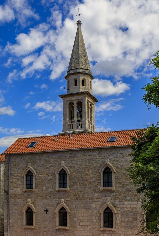 De Heilige Drievuldigheidskerk in de middeleeuwse Oude Stad van Budva met betrokken hemel op de achtergrond in Montenegro, de Bal stock fotografie