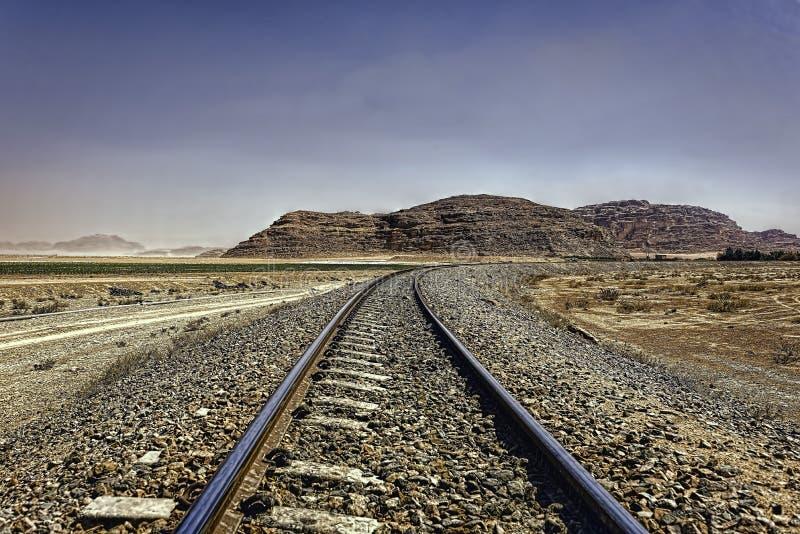 De Hejaz-Spoorweg onder wazige blauwe hemel in Wadi Rum-woestijn stock afbeeldingen