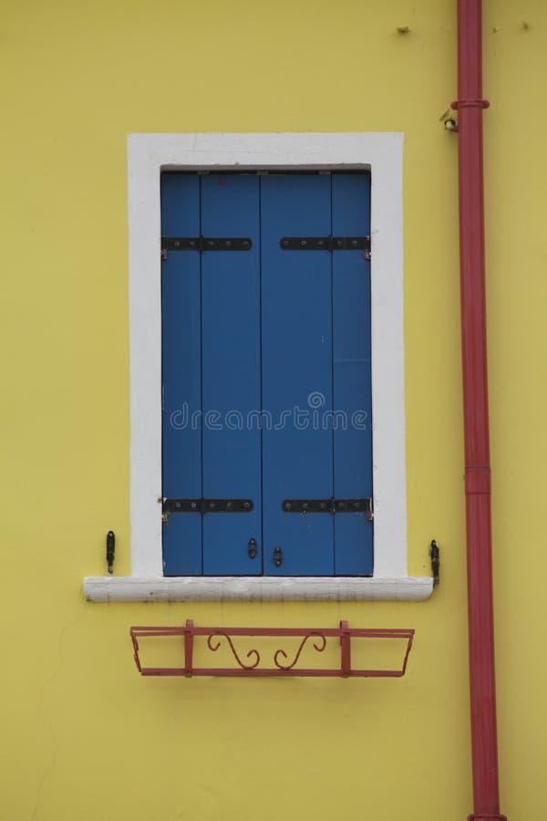 De helder gekleurde gele blinden en rode rioolbuis Burano Venetië van het muur blauwe venster royalty-vrije stock foto