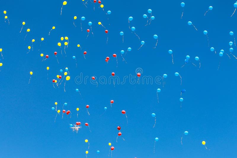 De heldere blauwe, rode en gele luchtballons stijgen in de blauwe hemel De achtergrond van ballen royalty-vrije stock foto