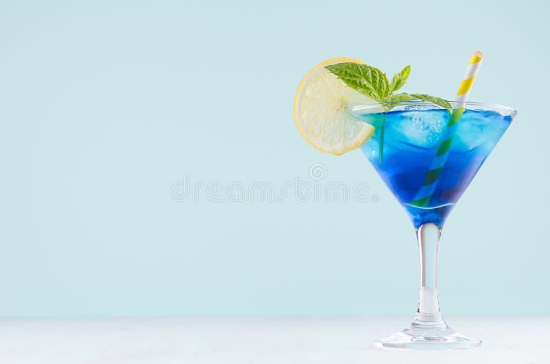 De heldere cocktail van het de zomer verse blauwe fruit met blauwe curacao alcoholische drank, ijsblokjes, citroenplak, groene mu royalty-vrije stock foto's