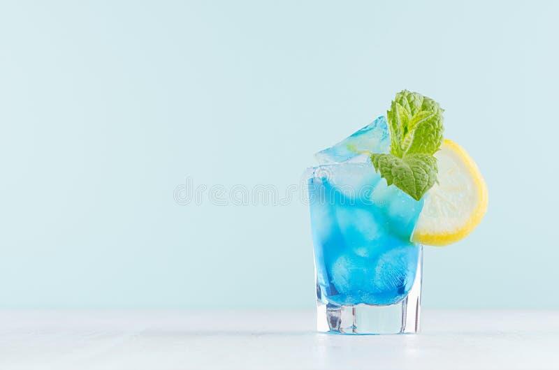De heldere cocktail van het de zomer verse blauwe fruit met blauwe curacao alcoholische drank, ijsblokjes, suikerrand, groene mun stock afbeeldingen