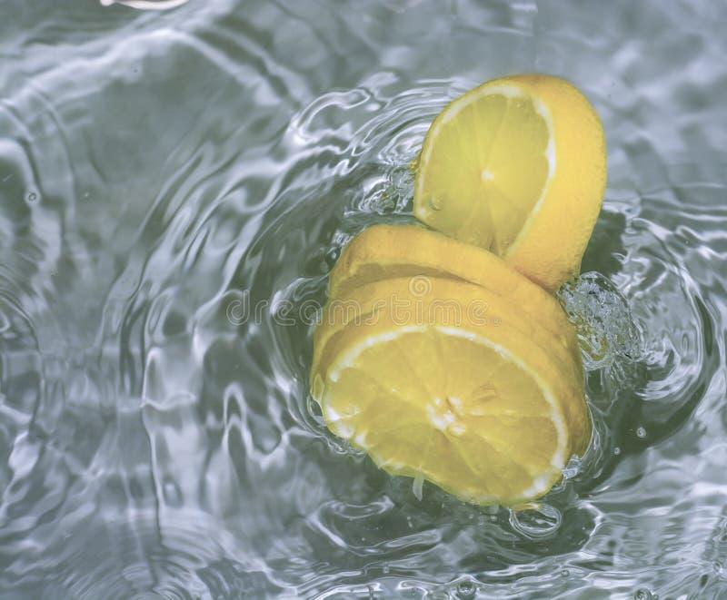 De heldere gele citroenen van het citroenenaandeel met water stock fotografie