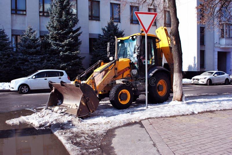 De heldere gele schoonmakende sneeuw van de graafwerktuigtractor op de weg langs straat, zijaanzicht, de sneeuwwinter in Kharkiv stock foto