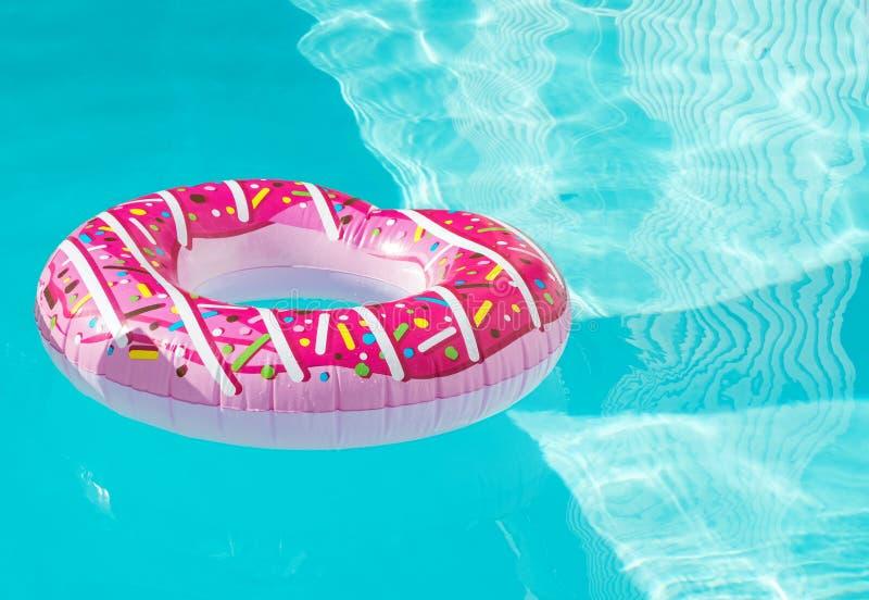 De heldere opblaasbare ring die van de doughnutvorm in het zwembad drijven stock afbeeldingen