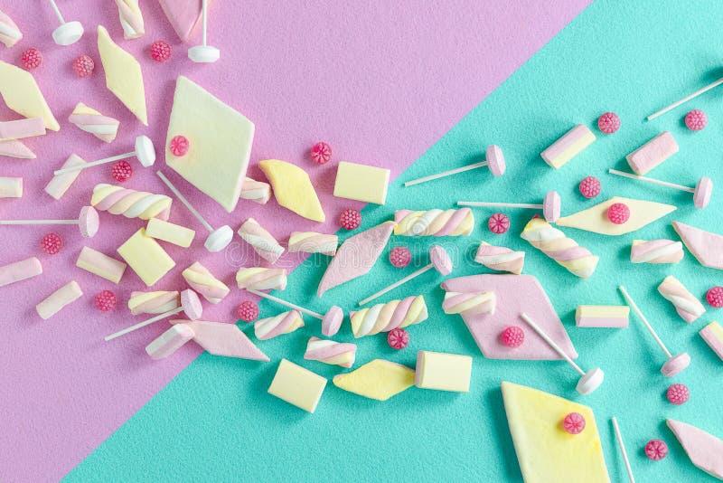 De heldere pastelkleur kleurde golf van pop heemstsuikergoed, lollie en frambozensnoepjes op een roze en turkoois gevoelde achter royalty-vrije stock afbeeldingen