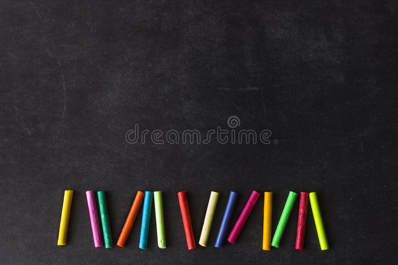 De heldere pastelkleurkleurpotloden liggen op een rij op een zwarte schoolraad Chil stock afbeeldingen