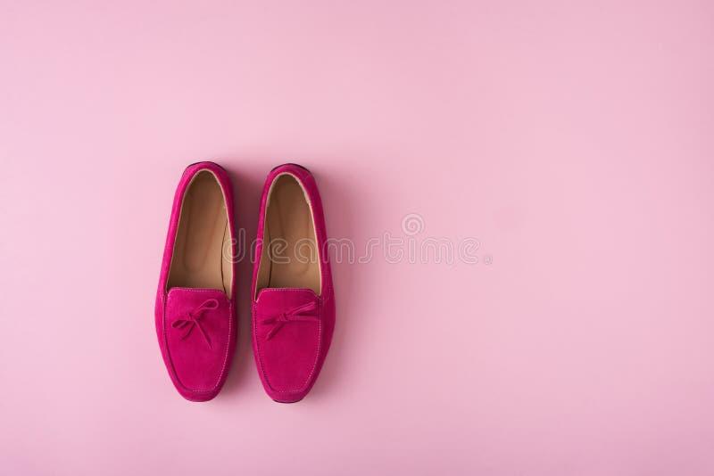 De heldere schoenen van het suèdemocassins van Frambozenclolor over roze achtergrond royalty-vrije stock fotografie