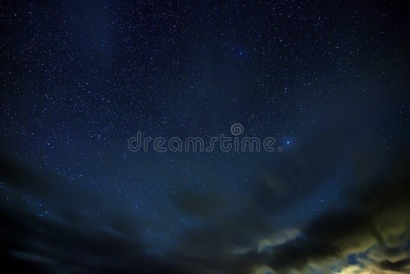 De heldere sterren glanzen door de wolken in de nachthemel stock foto's