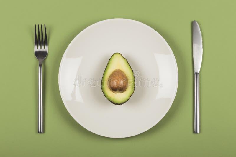De helft van avocado op een witte plaat met mes en vork stock afbeelding