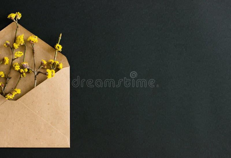 De helft van de envelop van ecodocument met gele bloemen op zwarte achtergrond stock afbeeldingen