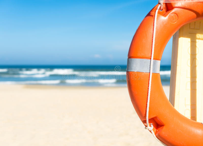 Zeegezicht met reddingsboei, blauwe hemel en zandig strand. stock foto's