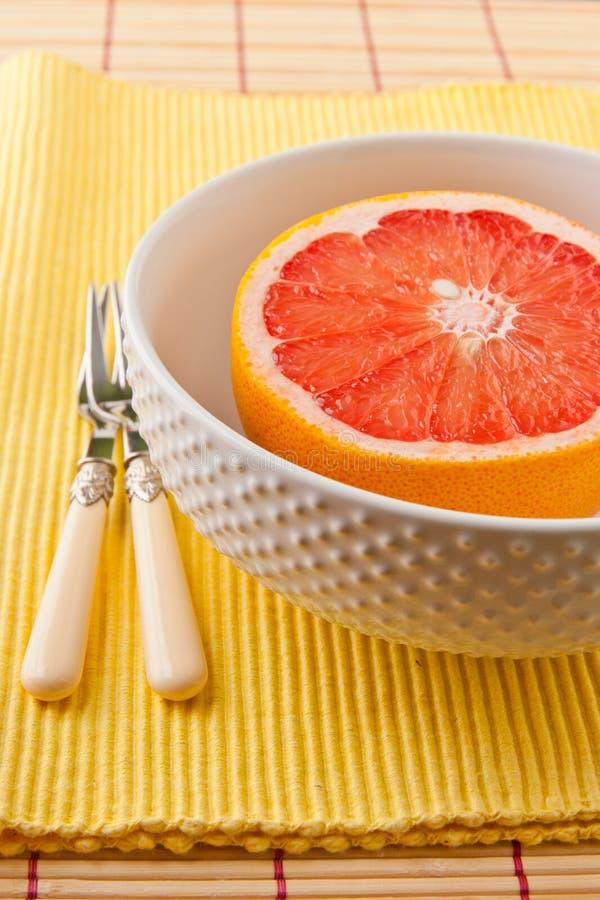De helft van robijnrode rode grapefruit in een kom klaar te eten. royalty-vrije stock fotografie