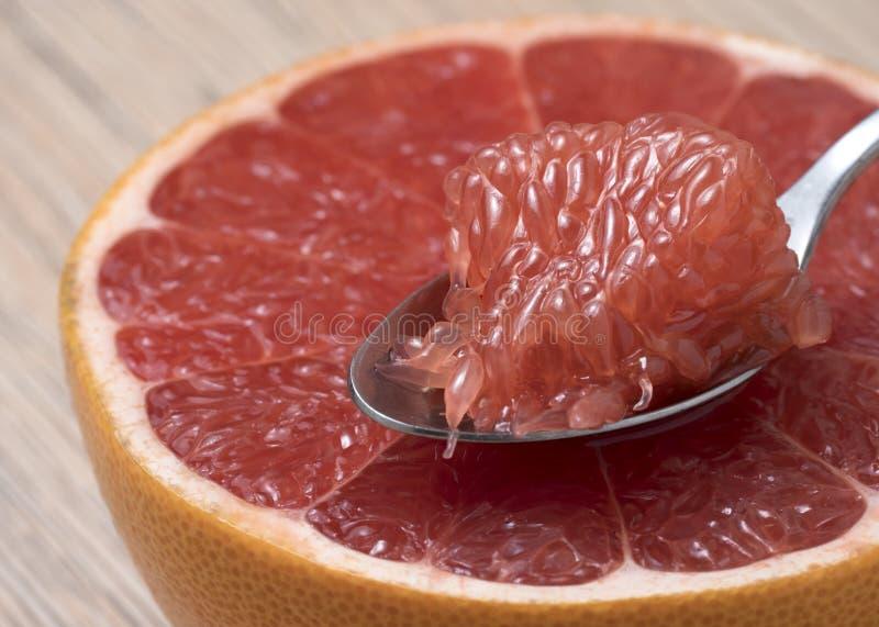 De helft van Sappige Rijpe Rode Grapefruit met plak in een lepel royalty-vrije stock fotografie