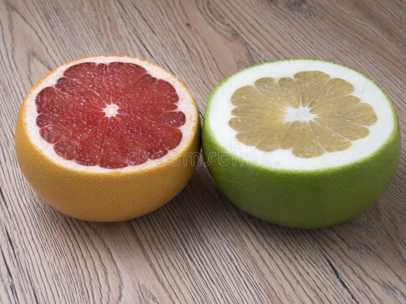 De helften van Groene Schat en Rode Grapefruit op houten achtergrond royalty-vrije stock afbeelding