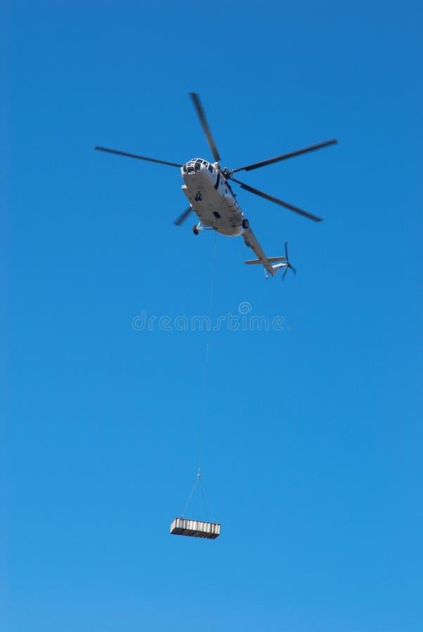 De helikopter van de vlieg met lading stock afbeelding