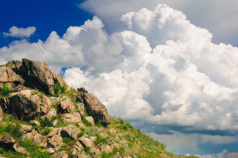 De helling van de bergsteen tegen de achtergrond van wolk stock foto