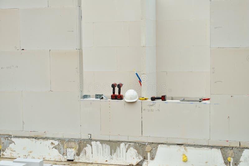 De helm en de arbeidershulpmiddelen van de veiligheid op bouwwerf stock foto's