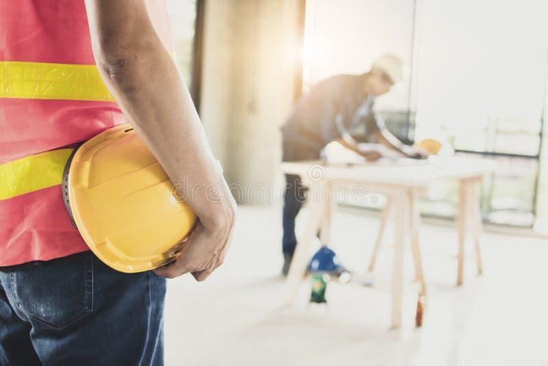 De helm van de arbeidersholding met ingenieur die aan lijst in construc werken stock afbeeldingen