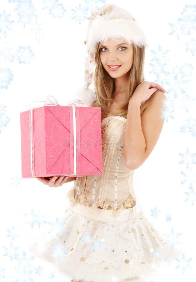 De helper van de kerstman in korset en rok met roze gift BO stock foto