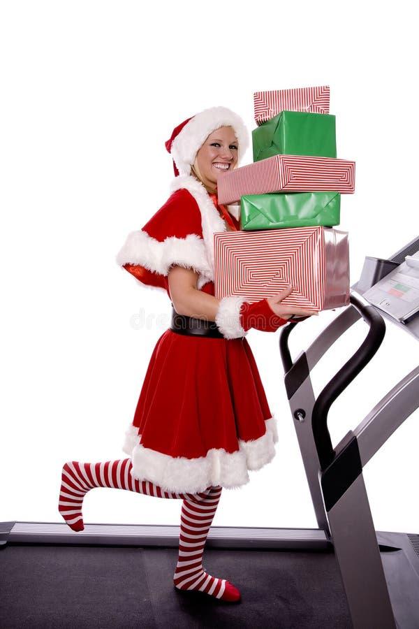 De helper van Santas op tredmolen met giften stock afbeelding