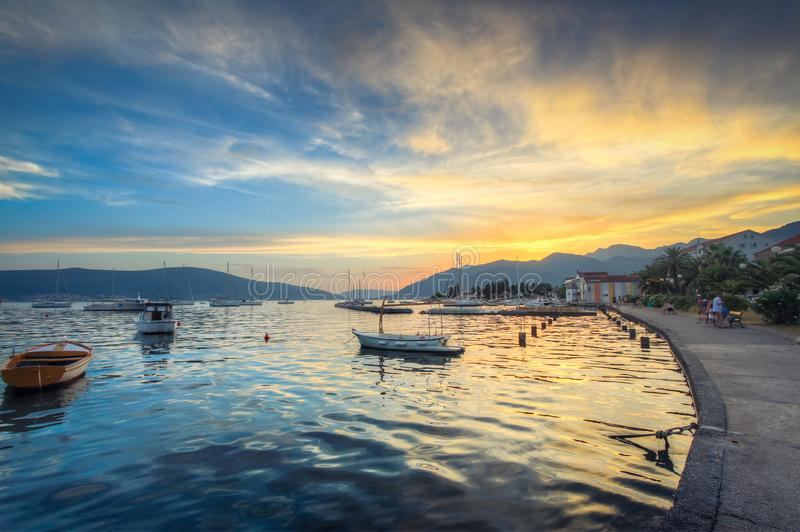 De hemel bij zonsondergang denkt in de paarlemoeren waterspiegel na, waarop de eenzame boten wandelen stock afbeeldingen