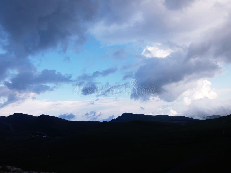 De hemel en de donkere bergheuvels royalty-vrije stock foto's