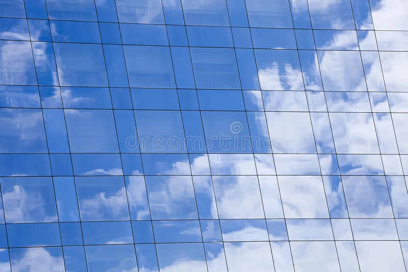 De hemel en de wolkenachtergrond overdachten de oppervlakte van de glasspiegel van een modern gebouw stock afbeelding