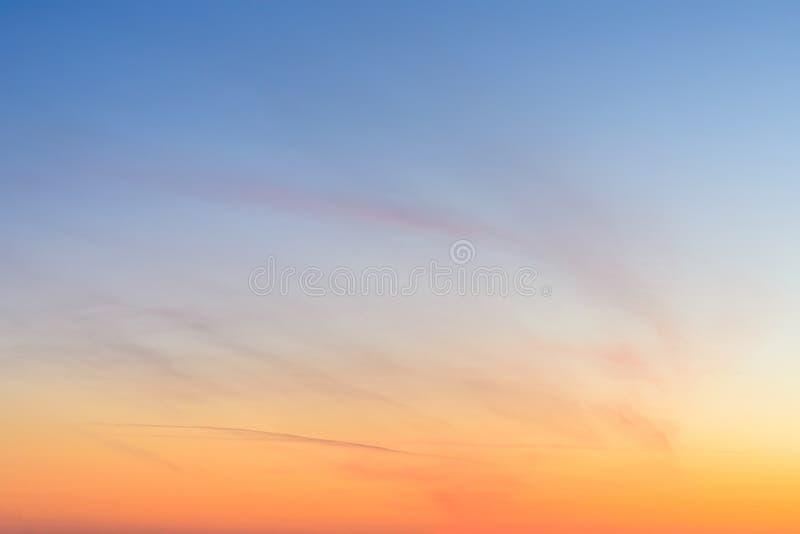 De hemel en de wolken bij zonsondergang, vatten kleurrijk achtergrond, sinaasappel en blauw samen stock fotografie